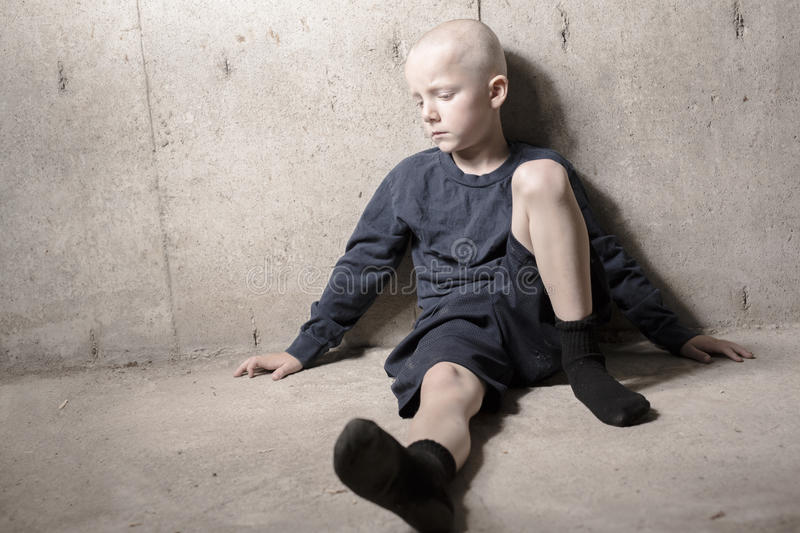 Neglected lonely child leaning at the wall stock photo
