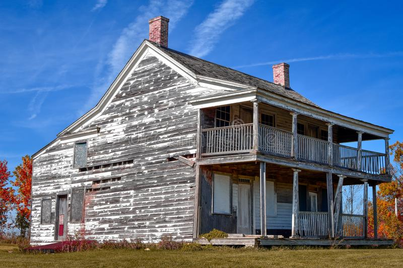 Neglected, Run-down House. A neglected, run-down, old two-story home with a front porch and balcony. This house has seen much better days stock image