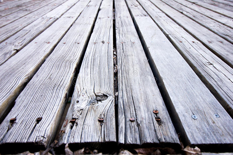 Neglected wooden deck. Old faded rotted wooden deck discolored to grey with splintering and dead leaves stock photos