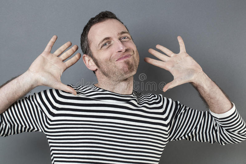 Negligence concept for coward 40s man smiling. Negligence concept - coward 40s man expressing exciting carefree responsibility for mistake,studio shot royalty free stock photos