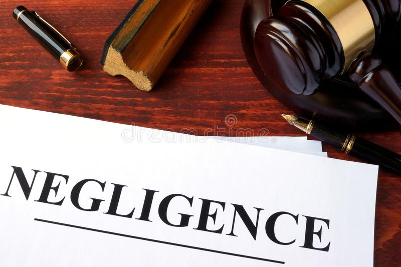 Negligence form and gavel on a table. Negligence form, documents and gavel on a table stock photos