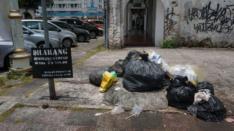 Negligencia de la advertencia del letrero El plástico pide y basura en el borde de la carretera imagenes de archivo