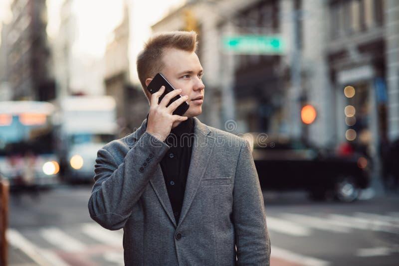 Negociações bem sucedidas do homem de negócios no telefone em uma rua ocupada da cidade de New York que veste um terno fotos de stock royalty free