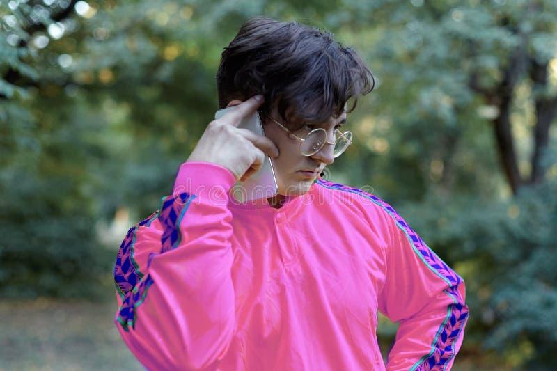 Negociações caucasianos consideráveis novas do homem no telefone celular que está no parque Vidros dourados redondos, camisa lilá imagens de stock royalty free