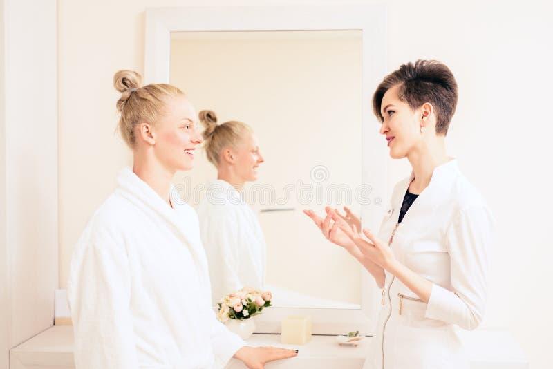 Negociações da mulher do doutor com o paciente a longo prazo e feliz Trabalhador m?dico no uniforme Conceito dos cuidados m?dicos foto de stock
