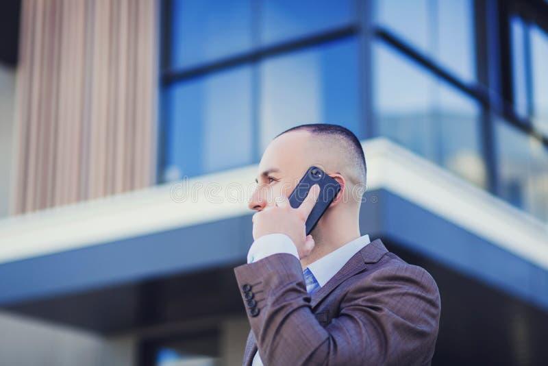 Negociações de homem de negócio no smartphone imagem de stock royalty free