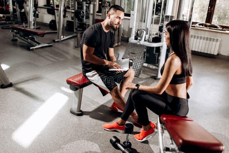 Negociações do treinador com a menina atlética vestida na roupa preta do esporte que senta-se no banco no gym imagens de stock royalty free