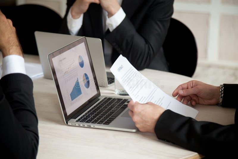 Negociações sob o contrato em uma reunião de três sócios, fim imagem de stock royalty free