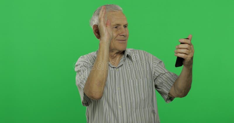 Negociaciones de hombre mayor sobre un smartphone Viejo hombre hermoso en el fondo dominante de la croma imagenes de archivo