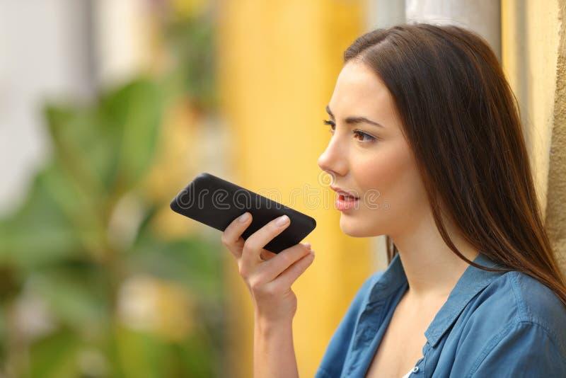 Negociaciones de la señora usando el reconocimiento vocal en el teléfono imagen de archivo