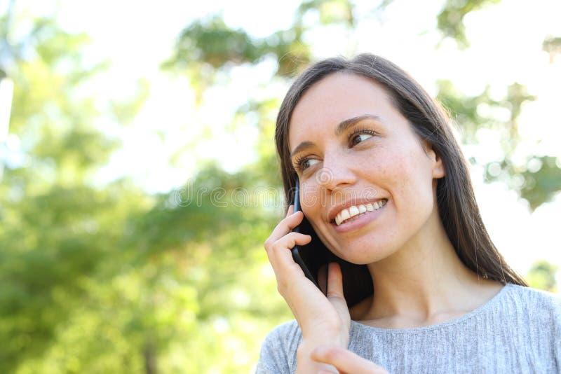 Negociaciones felices de la mujer sobre el teléfono en un parque foto de archivo libre de regalías