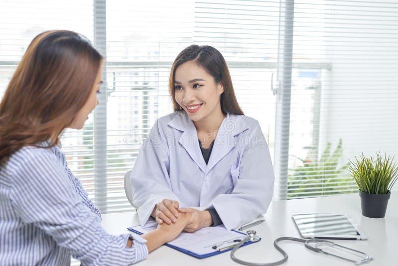 Negociaciones femeninas del doctor al paciente femenino en el rato w de la oficina del hospital imagenes de archivo