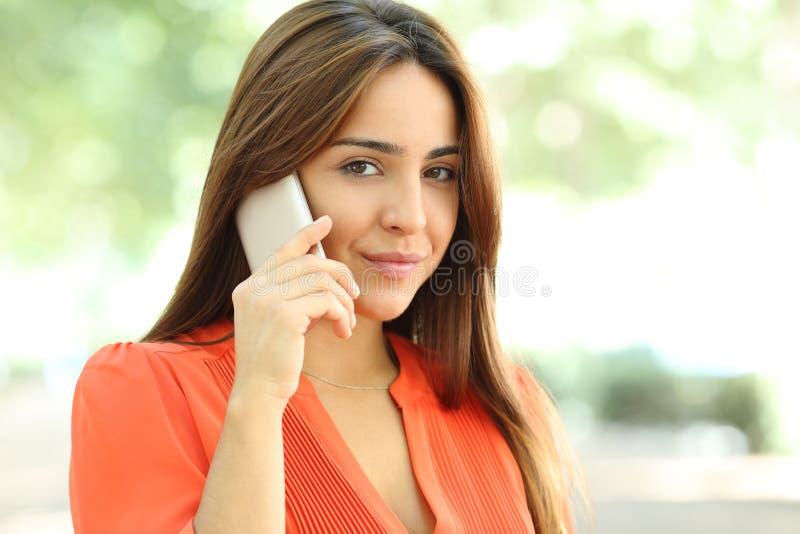 Negociaciones serias de la mujer sobre el teléfono que mira la cámara foto de archivo