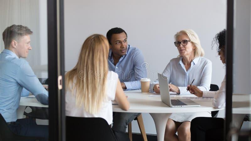Negociadores internacionais ou negócio de fala do pessoal de escritório diverso na sala de reuniões fotos de stock