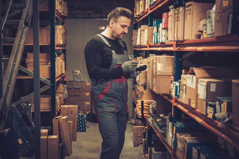 Negociante com o varredor handheld do código de barras que trabalha em um armazém foto de stock