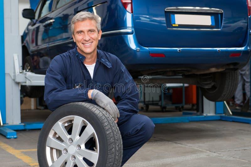 Negociante do pneumático que guarda um pneu imagem de stock