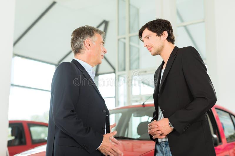 Negociante e homem novo com o automóvel no concessionário automóvel foto de stock royalty free