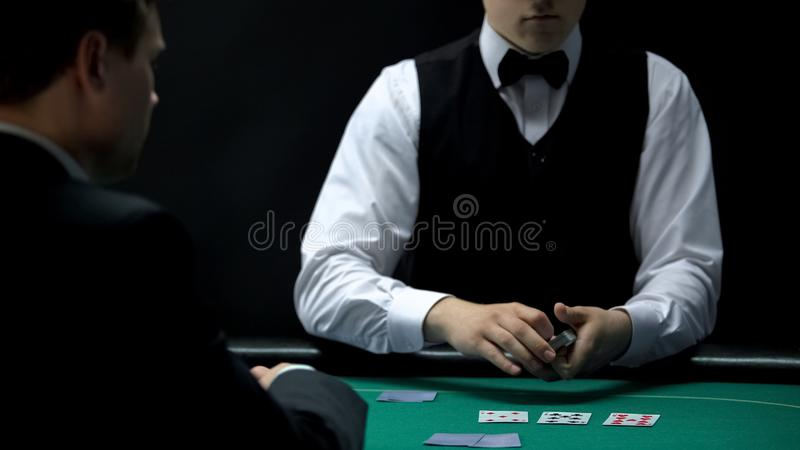 Negociante profissional do casino que coloca cartões na tabela verde para o cliente, jogo de pôquer imagem de stock