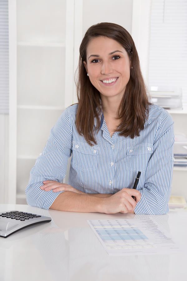 Negocio acertado: mujer que sonríe en la blusa azul que se sienta en el DES imagenes de archivo