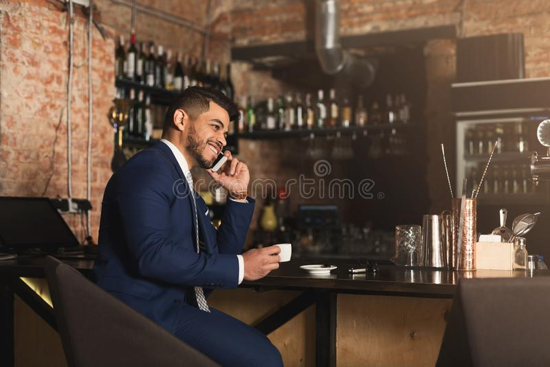 Negocio alegre que habla en el teléfono en barra imagen de archivo libre de regalías