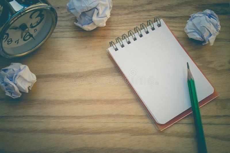Negocio creativo y concepto de la idea: El lápiz verde usado puesto en el cuaderno con blanco arrugó la bola de papel puesta en l foto de archivo libre de regalías