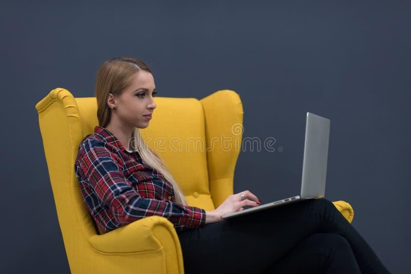 Negocio de lanzamiento, mujer que trabaja en el ordenador portátil y que se sienta en amarillo imagen de archivo libre de regalías