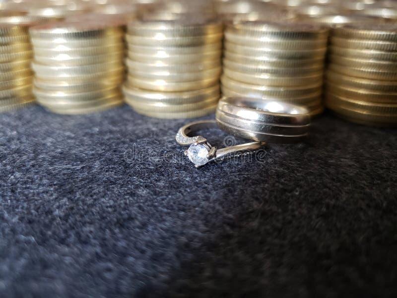 negocio del oro y del metal, anillo de compromiso y matrimonio con las monedas de oro apiladas imagenes de archivo
