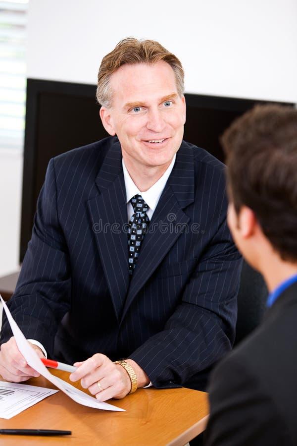 Negocio: Empleado de Reviewing Documents With del encargado fotos de archivo