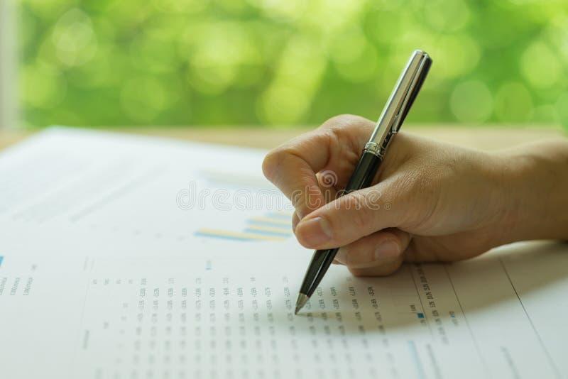 Negocio, inversión o estudio de informe financiero, pluma de tenencia de la mano que revisa informe de las finanzas con la impres fotos de archivo