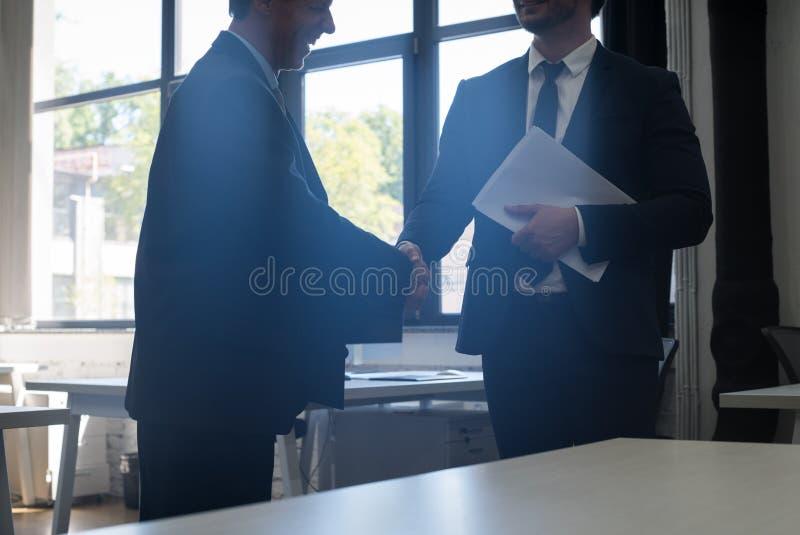 Negocio irreconocible Team Coworkers del centro de Coworking del acuerdo de la mano de la sacudida del hombre de negocios dos imagenes de archivo