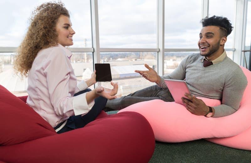 Negocio Team Coworkers Sitting del centro de Coworking de la comunicación de los pares de los empresarios en ventana panorámica g imagen de archivo libre de regalías