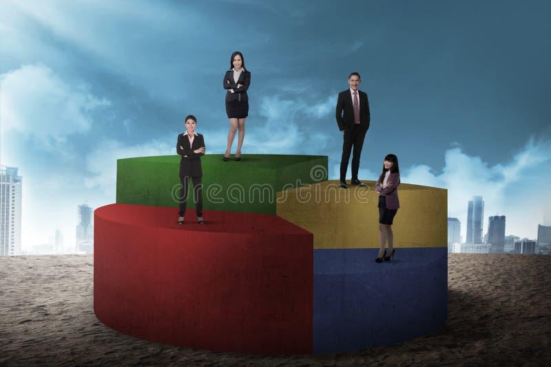 Negocio Team Standing On Pie Chart fotografía de archivo