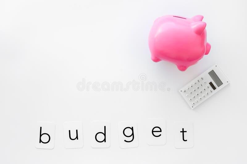 Negocio y concepto del presupuesto con la hucha y la calculadora en la maqueta blanca de la opinión de top del fondo de la oficin foto de archivo