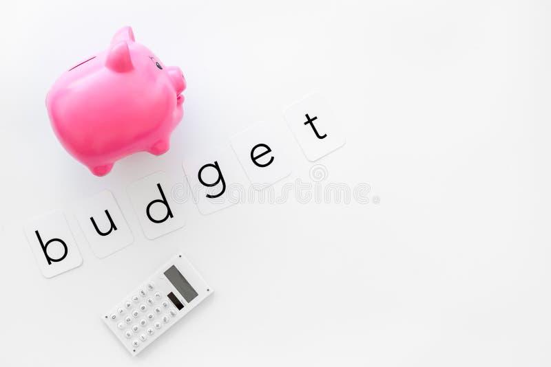 Negocio y concepto del presupuesto con la hucha y la calculadora en la maqueta blanca de la opinión de top del fondo de la oficin imagen de archivo