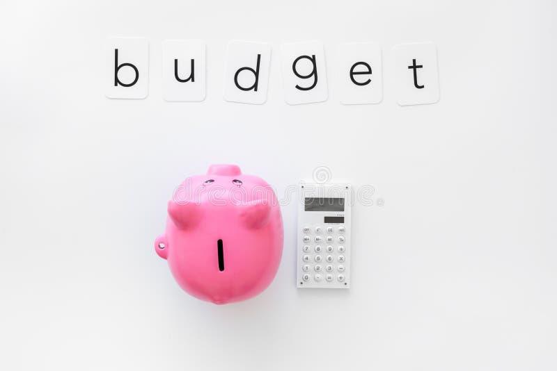 Negocio y concepto del presupuesto con la hucha y la calculadora en la opinión de top blanca del fondo de la oficina fotografía de archivo