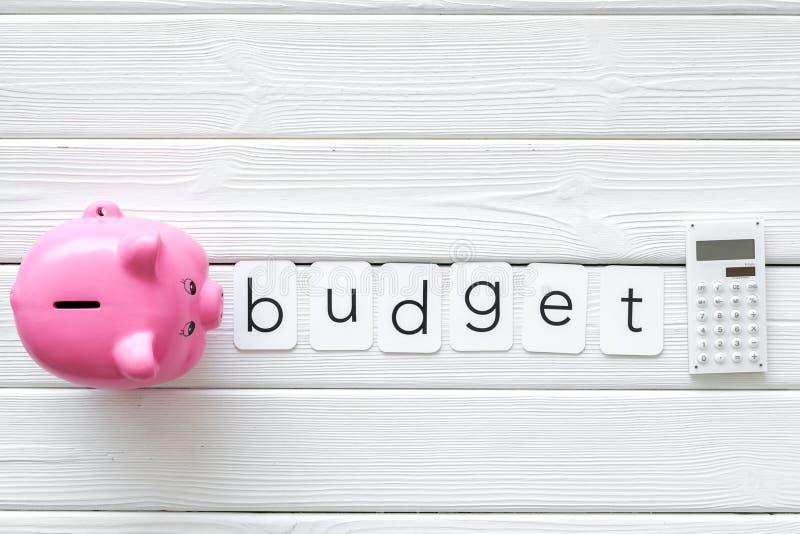 Negocio y concepto del presupuesto con la hucha y la calculadora en la opinión de top de madera blanca del fondo de la oficina imagen de archivo