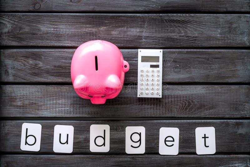 Negocio y concepto del presupuesto con la hucha y la calculadora en la opinión de top de madera del fondo de la oficina imagen de archivo libre de regalías