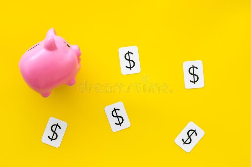 Negocio y concepto del presupuesto con la muestra de la hucha y de dólar en la opinión superior del fondo amarillo imagen de archivo libre de regalías