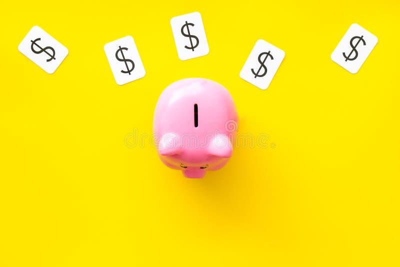 Negocio y concepto del presupuesto con la muestra de la hucha y de dólar en la opinión superior del fondo amarillo fotos de archivo libres de regalías