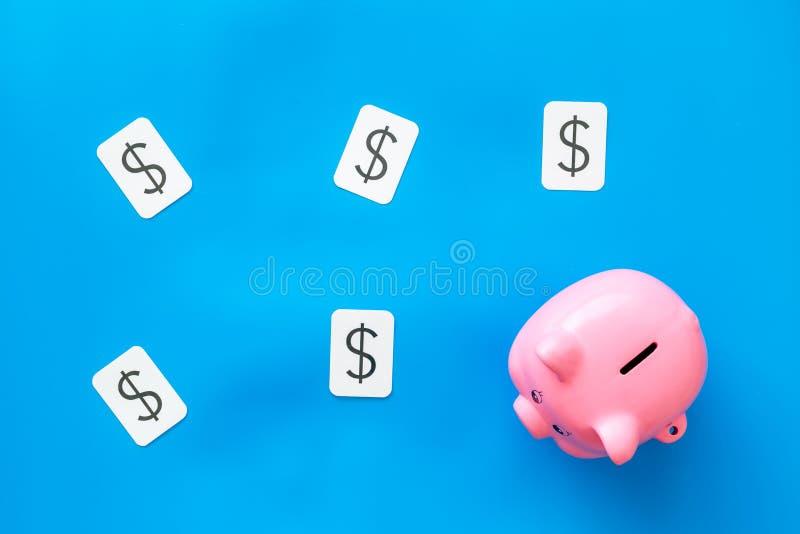 Negocio y concepto del presupuesto con la muestra de la hucha y de dólar en la opinión superior del fondo azul imagen de archivo