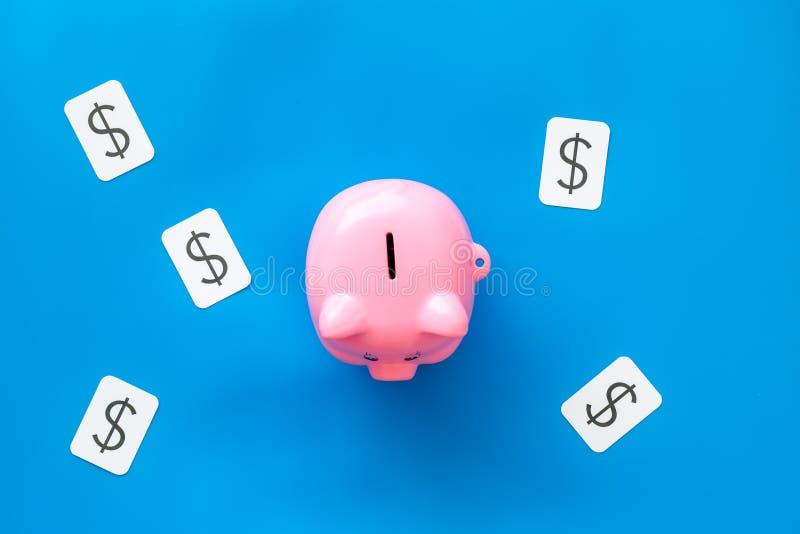 Negocio y concepto del presupuesto con la muestra de la hucha y de dólar en la opinión superior del fondo azul fotos de archivo