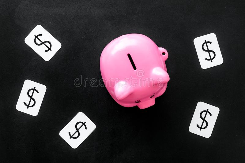 Negocio y concepto del presupuesto con la muestra de la hucha y de dólar en la opinión superior del fondo negro imagen de archivo libre de regalías