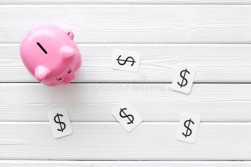 Negocio y concepto del presupuesto con la muestra de la hucha y de dólar en la opinión de top de madera blanca del fondo imagen de archivo