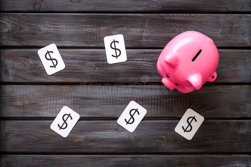 Negocio y concepto del presupuesto con la muestra de la hucha y de dólar en la opinión de top de madera del fondo de la oficina imagenes de archivo