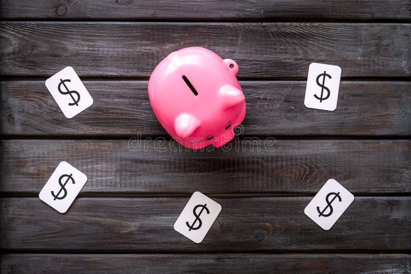 Negocio y concepto del presupuesto con la muestra de la hucha y de dólar en la opinión de top de madera del fondo de la oficina fotografía de archivo