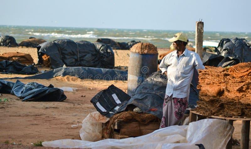 NEGOMBO, SRI LANKA, febrero de 2018: El hombre que se coloca en la playa en el mercado de pescados entre las redes de pesca almac imágenes de archivo libres de regalías