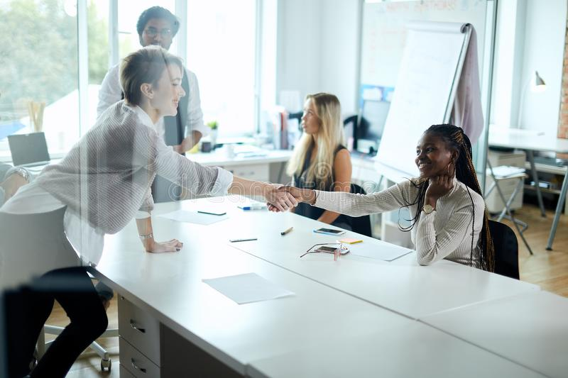 Negotiating business, awesome mixed race girls shaking hands after successful contract royalty free stock photo