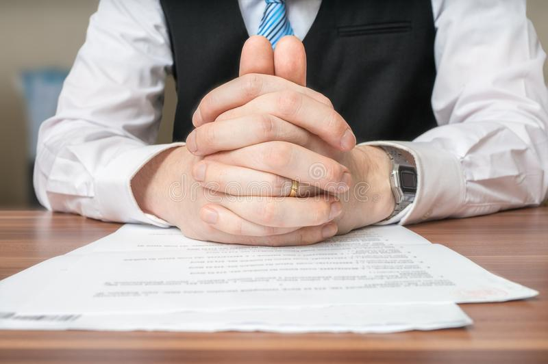 Negotiation with lawyer who is sitting behind desk and has clasped hands stock photo