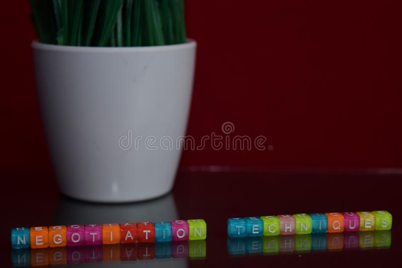Negotiation techniques text at colorful wooden block on red background. Desk office and education concept stock image