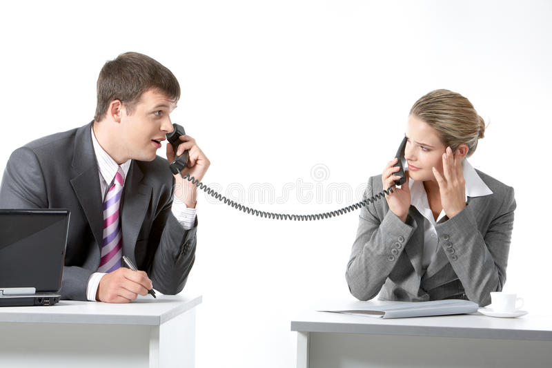 Negotiations. Portrait of business partners speaking on the telephone and looking at each other royalty free stock photos